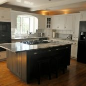 Updated kitchen with white cabinets, dark island cabinets, and gray countertops - St Croix Cabinet Solutions