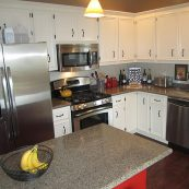 Kitchen with white custom cabinets, gray countertop, and dark floors - St Croix Cabinet Solutions
