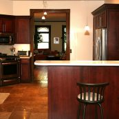 Kitchen with dark custom cabinets, white countertop, and tile floors - St Croix Cabinet Solutions