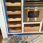 Custom cabinet storage next to oven with pull-out drawers - St Croix Cabinet Solutions