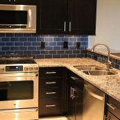 Modern kitchen with dark cabinets and blue backsplash - St Croix Cabinet Solutions