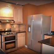 Kitchen with white custom cabinets and dark gray cabinets - St Croix Cabinet Solutions