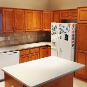 Kitchen with brown cabinets and white countertop - St Croix Cabinet Solutions