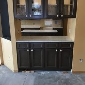 Kitchen remodel with passthrough, dark cabinets, and light countertops - St Croix Cabinet Solutions