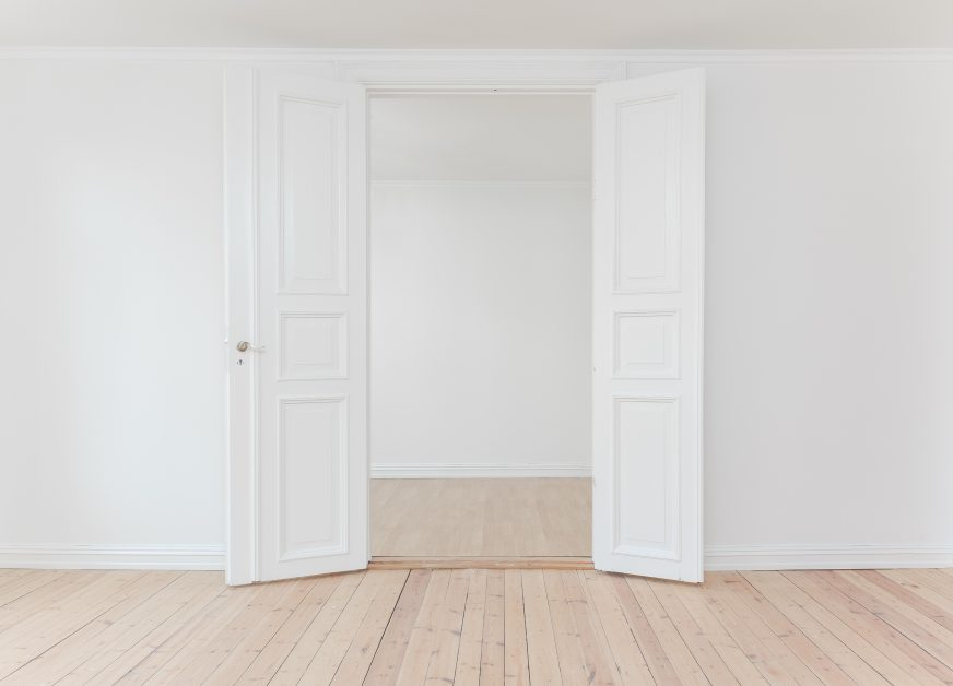 An image of a new home with two white doors open.