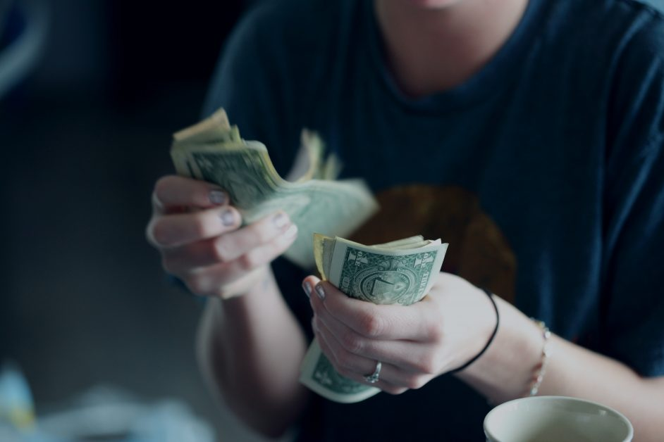 An image of a person counting money.