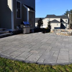A unique stone patio architectural design in Walpole by StonePro Builders