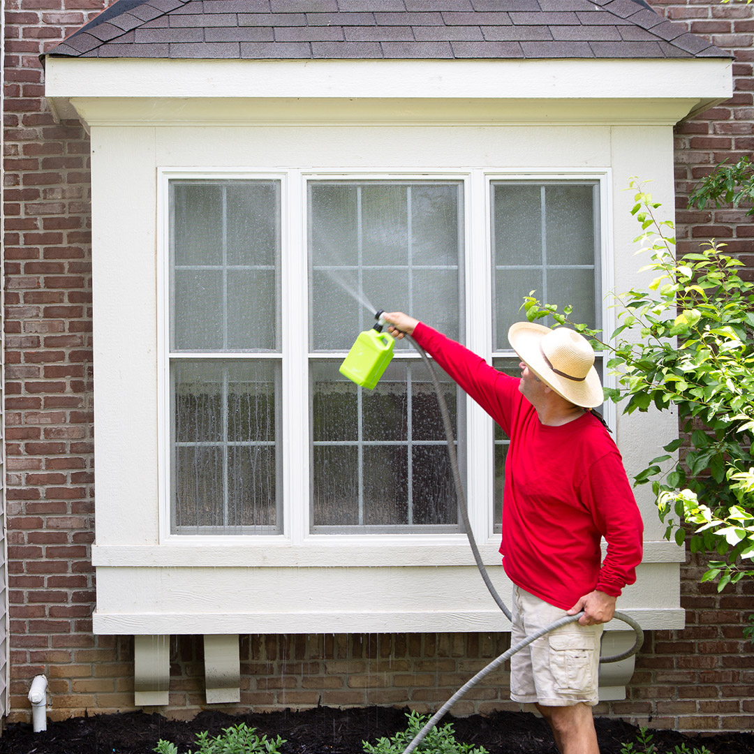 Man in a red shirt and hat spraying the front windows of a home with a power washer.