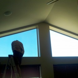 Applying solar window film to vaulted residential windows.