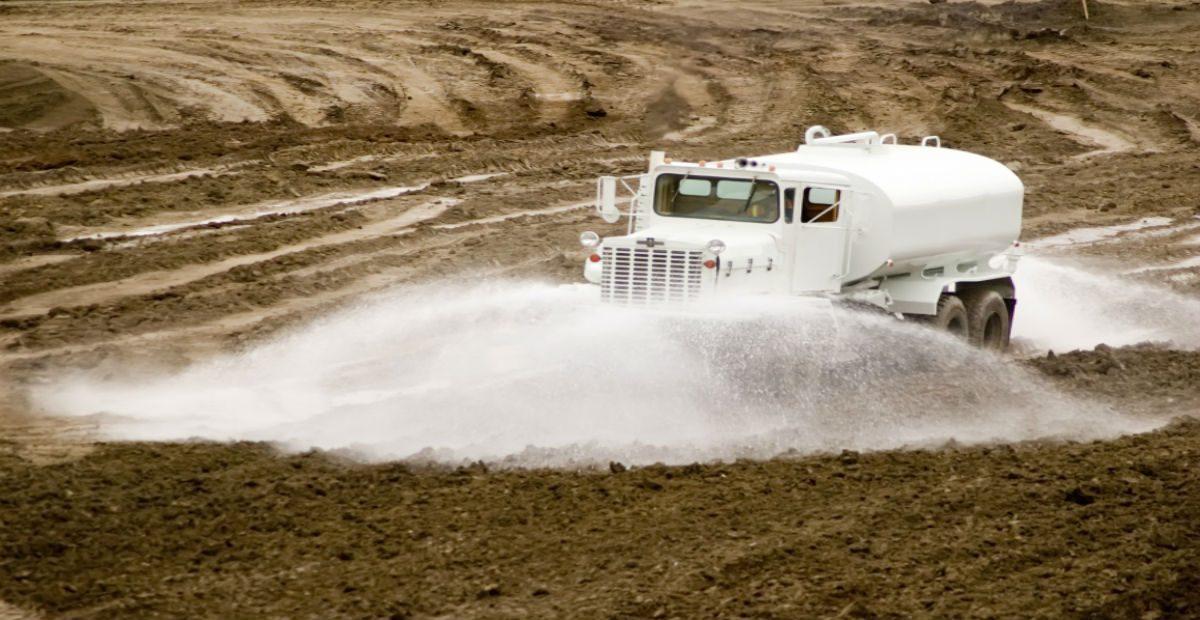 Water truck spraying water in a field