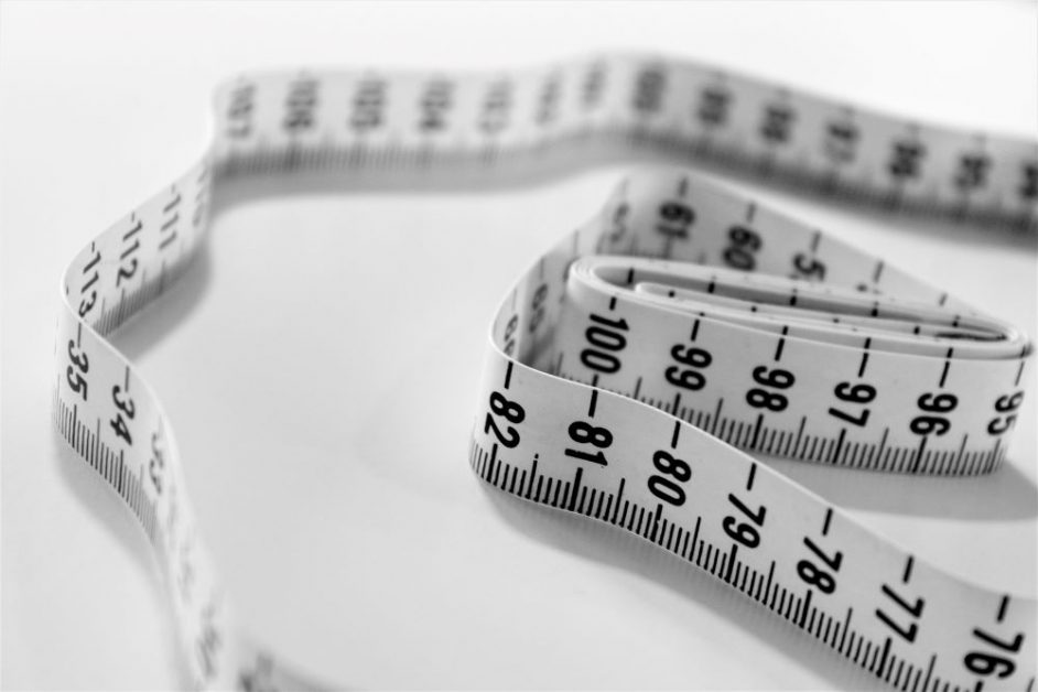 Selective focus photography of a white and black measuring tape used to assess body weight. Photo by Siora Photography on Unsplash.