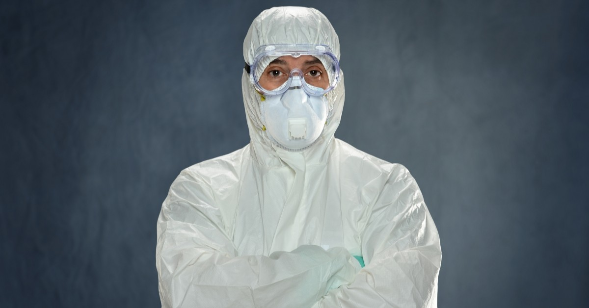A laboratory technician crossing his arms and looking at the camera