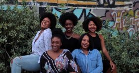 Photo of five women with natural hair sitting outside by Leighann Blackwood on Unsplash
