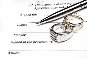 prenuptial agreement with pen and wedding rings on top of it