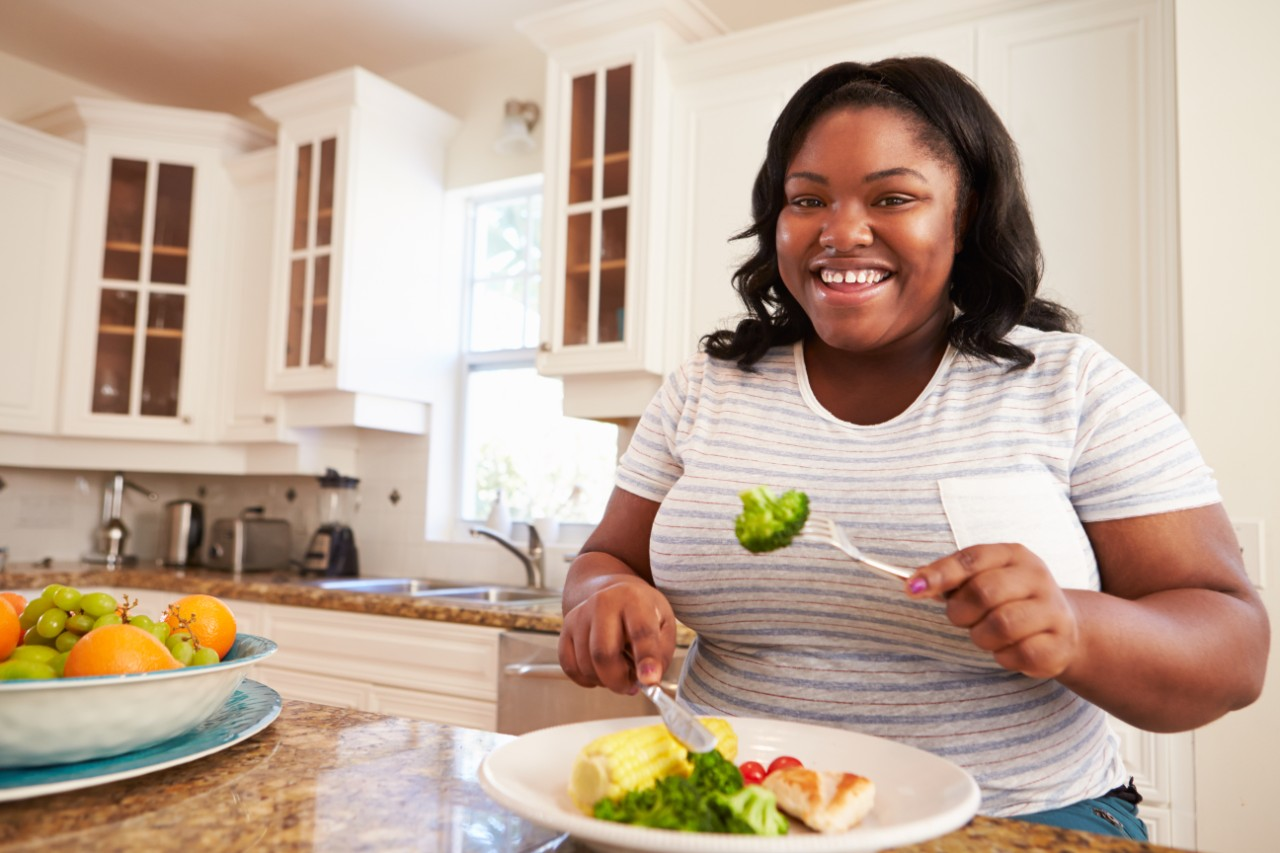 heavy-set black women smiling in front of a plate of healthy food options