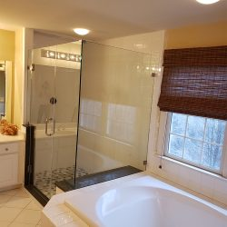 Custom glass shower doors next to a white bath tub