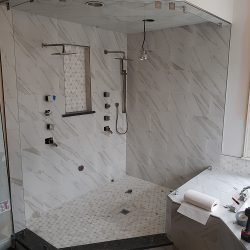 Installing custom glass shower doors on a shower with grey and white tile