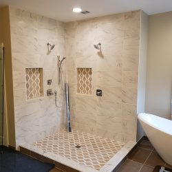 Preparing to install custom glass shower doors on a shower with beige tile
