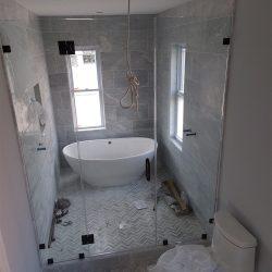 Custom shower doors around a shower and bath tub
