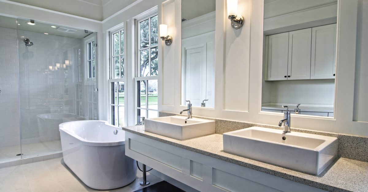Bathroom with mirrors, sink, bathtub, and lights
