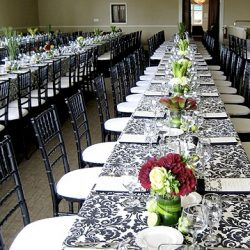 Wedding reception with banquet tables, black and white table cloth, and black Chiavari chairs - The Rented Event