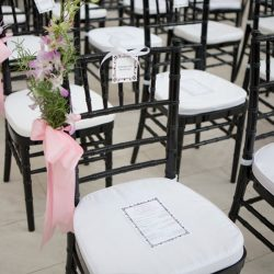 Rows of black Chiavari chairs with white cushions and pink bows - The Rented Event