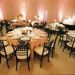 Reception space with ivory tables and black Chiavari chairs - The Rented Event