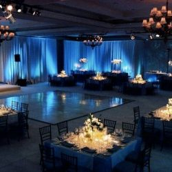 Wedding reception space with dance floor and tables with lights - The Rented Event