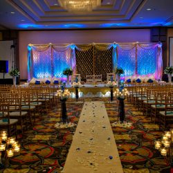 Wedding ceremony decorated with Chiavari chairs, flower petals, and candles - The Rented Event