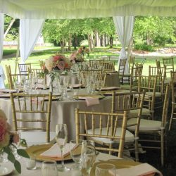 An outdoor wedding reception tent with tables and gold Chiavari chairs - The Rented Event