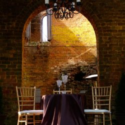 Wedding table with Chiavari chairs and brick background - The Rented Event
