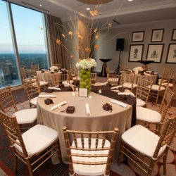 A wedding table with gold Chiavari chairs and large window - The Rented Event