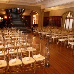 A wedding ceremony room with gold Chiavari chairs - The Rented Event