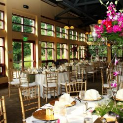 A large wedding reception room with tables and gold Chiavari chairs - The Rented Event