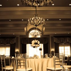 A wedding table with Chiavari chairs and chandeliers - The Rented Event