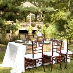 Outdoor wedding reception table with white table cloths and mahogany Chiavari chairs - The Rented Event