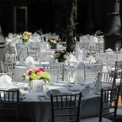 Outdoor reception with white tables and silver Chiavari chairs - The Rented Event