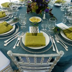 Wedding reception table with teal and green colors and silver Chiavari chairs - The Rented Event