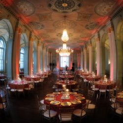 Wedding reception hall with tables decorated with red - The Rented Event