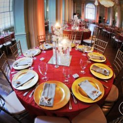 A wedding reception table with red table cloth and gold accents - The Rented Event