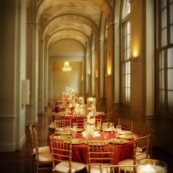 Elegant wedding reception hall with red table cloths and gold Chiavari chairs - The Rented Event