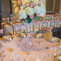 A wedding reception table with floral centerpiece and gold accents - The Rented Event