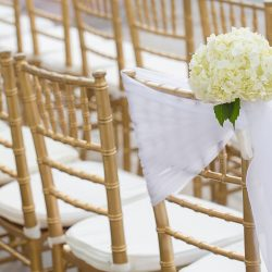 Gold Chiavari chairs and center aisle chair with floral bouquet - The Rented Event