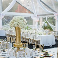 Wedding reception tent with tables, centerpiece, and gold Chiavari chairs - The Rented Event