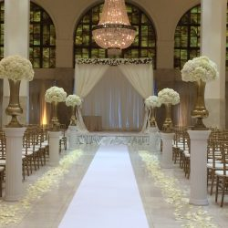Wedding ceremony decorated with floral petals, gold Chiavari chairs, and columns - The Rented Event