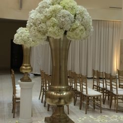 Wedding ceremony decorated with columns, floral pieces, and gold Chiavari chairs - The Rented Event