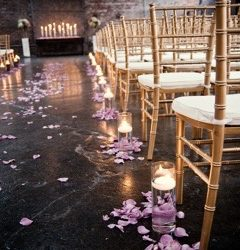 Detail of a wedding aisle with Chiavari chairs and flower petals - The Rented Event