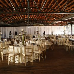 Large wedding reception space with ivory tables and Chiavari chairs - The Rented Event