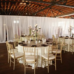 Wedding reception space with tables and gold Chiavari chairs - The Rented Event