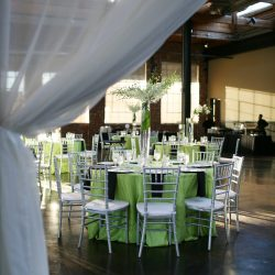 Wedding reception with green colors and silver Chiavari chairs - The Rented Event